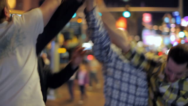 four friends hang out together on the las vegas strip. - high five stock videos & royalty-free footage