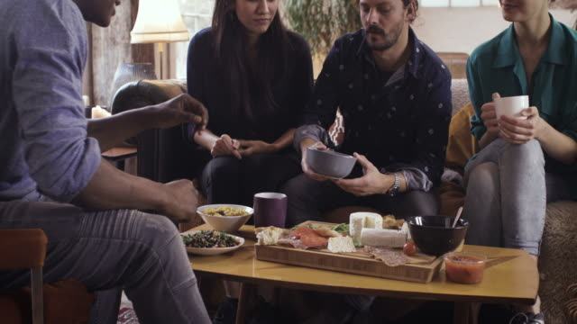 vídeos de stock, filmes e b-roll de four friends hanging out talking & eating food at home - top