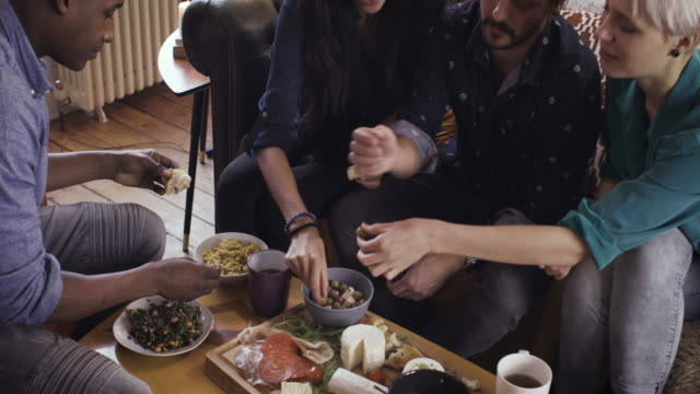 vídeos de stock, filmes e b-roll de four friends hanging out talking & eating food at home - 30 39 years