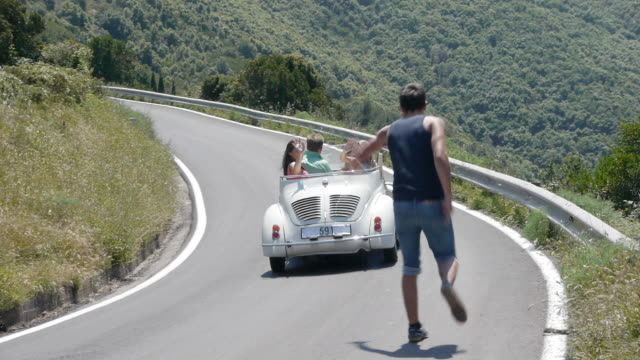 Four friends in convertible driving past hitchhiker