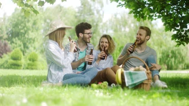 ビールを飲んで自然にピクニックに 4 人の友人