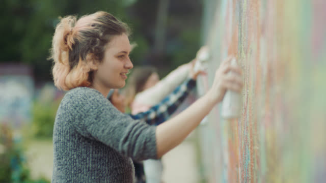 MS. Four friends paint with spray cans on graffiti wall in Austin park.