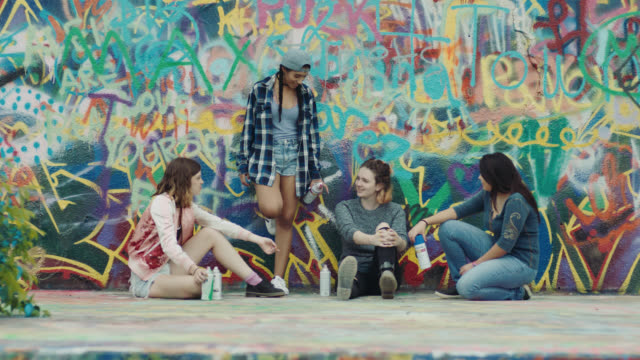 WS. Four friends sit against graffiti wall and talk in urban street art park.
