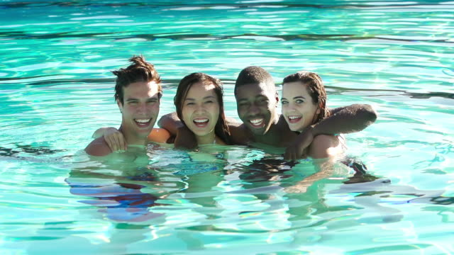 Four friends swimming at an outdoor pool
