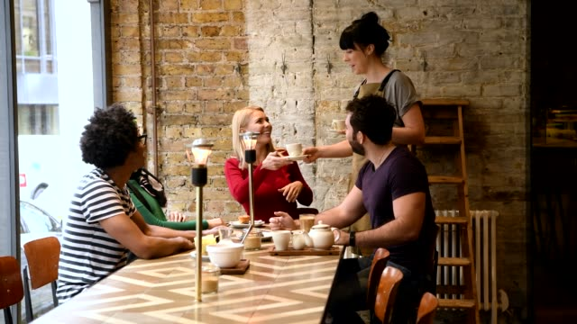 Four friends talking in coffee shop and waitress bringing drinks