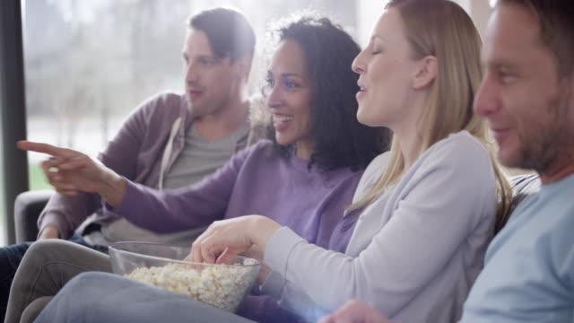 vídeos de stock, filmes e b-roll de quatro amigos assistindo tv e se divertindo - pipoca