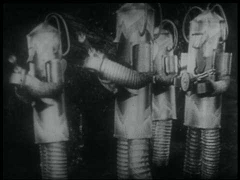 B/W 1936 four futuristic robots shooting ray guns