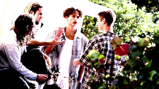 OVEREXPOSED CANTED four Generation X teen boys shaking hands + greeting each other outdoors