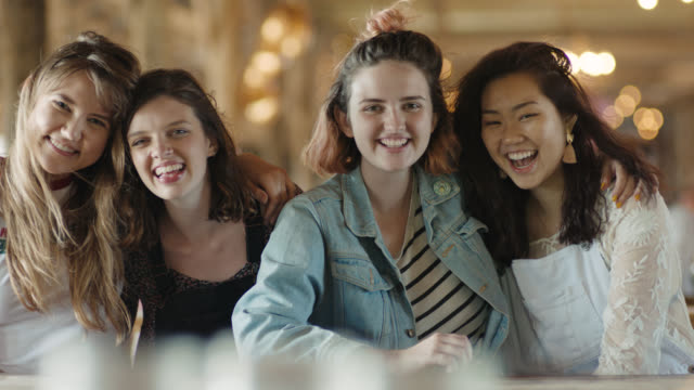 MS SLO MO. Four girl friends laugh together and smile at camera.