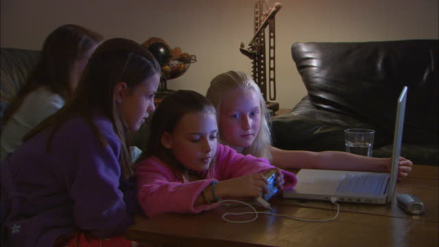 cu, four girls (10-11) downloading pictures from digital camera into laptop - loading stock videos & royalty-free footage