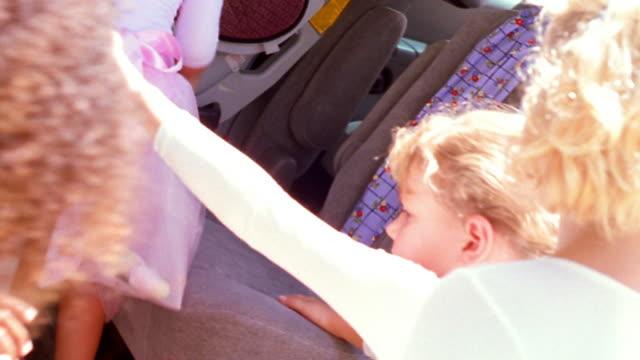 vídeos de stock e filmes b-roll de canted ms four girls in leotards getting in minivan + fastening seat belts / florida - body de ginástica