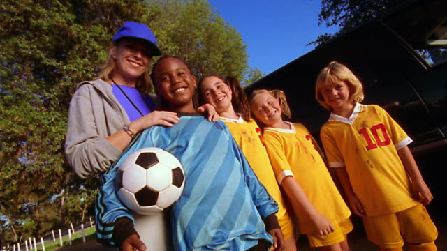 canted ms portrait four girls in soccer uniforms with soccer mom/coach standing outdoors - blonde hair stock videos & royalty-free footage