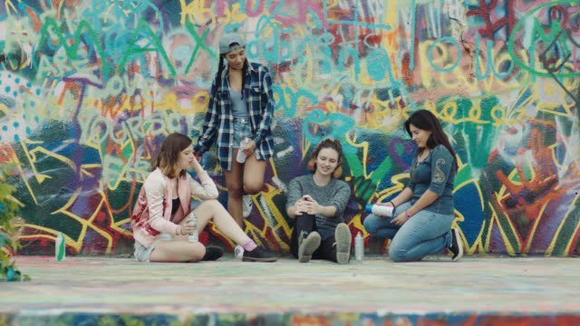 vídeos de stock e filmes b-roll de ws. four girls leaning against graffiti wall talk and laugh in urban street art park. - grafite produto artístico