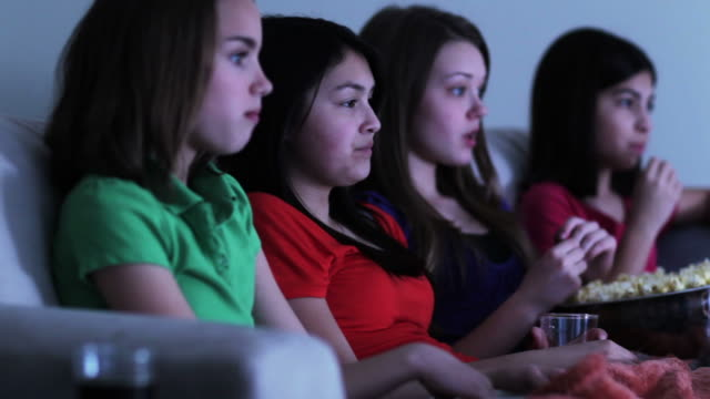 four girls on sofa eating popcorn watching funny movie - nur weibliche teenager stock-videos und b-roll-filmmaterial