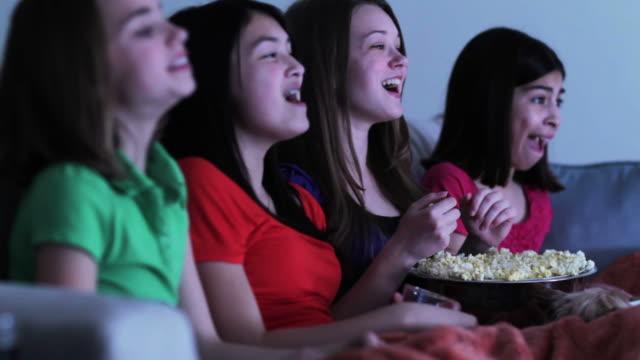 vídeos de stock e filmes b-roll de four girls on sofa eating popcorn watching funny movie - só meninas adolescentes