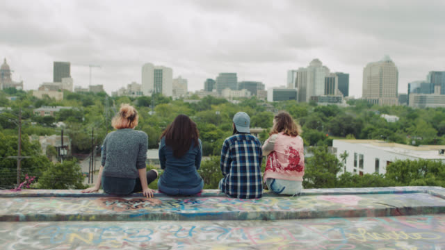WS. Four girls sit and talk on graffiti wall overlooking Austin city skyline.