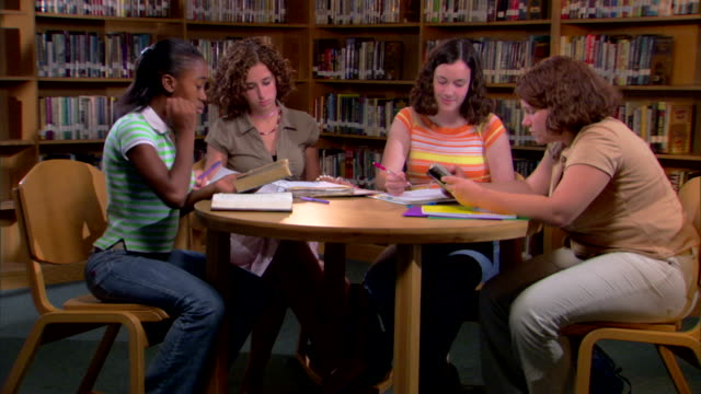 vidéos et rushes de four girls sit at a round table studying in the library. - 16 17 ans
