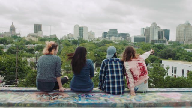 WS. Four girls sit on graffiti wall overlooking downtown Austin and point out at city skyline.