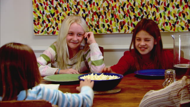 vidéos et rushes de zi, cu, four girls (10-11) sitting at table and laughing, one talking on phone - téléphone sans fil