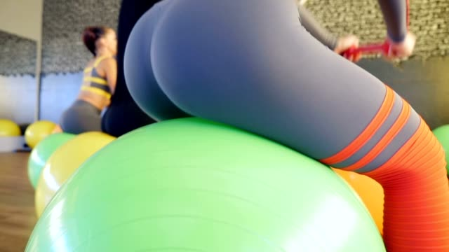 four girls train buttocks jumping on balls in the gym