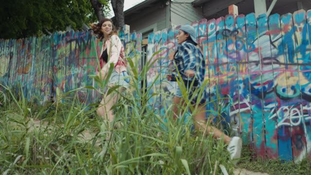 WS SLO MO. Four girls walk uphill past graffiti fence in urban park.
