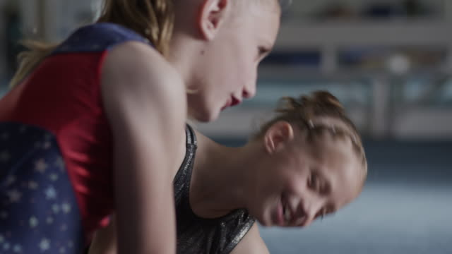 cu pan four girls (8-9, 10-11) wearing leotards laughing and talking in gym, orem, utah, usa - leotard stock videos and b-roll footage