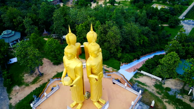 four golden buddha statue close up toward, aerial view from drone at wat doi sappanyoo temple, chiangmai, thailand. - temple building stock videos & royalty-free footage
