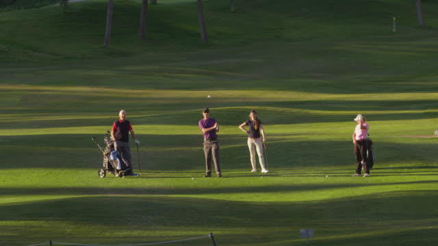 LS four golfers (mature and young couple) on fairway, young man plays ball to camera, RED R3D 4K