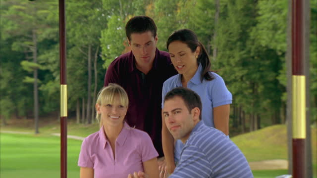 ms, zi, four golfers posing sitting at outdoor table, seco, maine, usa - maglietta polo video stock e b–roll