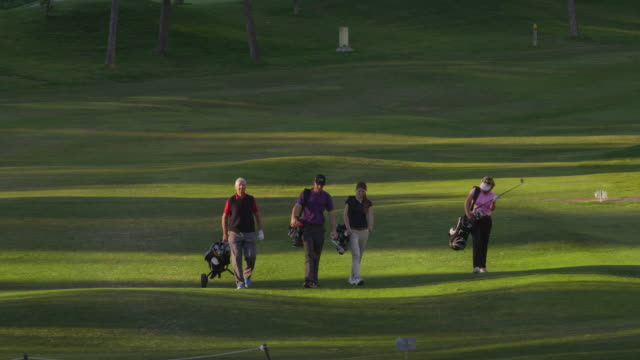 ls four golfers (mature and young couple) walking along fairway in last light of day in direction of camera, red r3d 4k - golf glove stock videos and b-roll footage