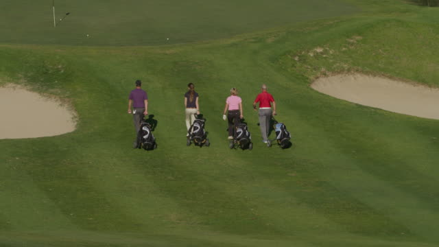 ls tu four golfers (young and mature couples) walking  with their caddies along golf course to green, park their caddies and prepare to putt, red r3d 4k - golfer stock videos and b-roll footage
