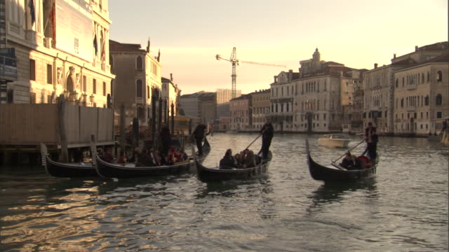 four gondolas travel on the grand canal in venice, italy. - traghetto video stock e b–roll