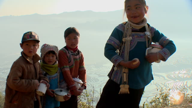 MS MONTAGE Four Hani children holding cooking pots, rice paddies in background, Yuanyang, Yunnan, China