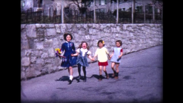 1965 four happy girls skipping down the street - innocenza video stock e b–roll