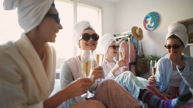 four happy young girlfriends celebrating their friendship with glasses of champagne at a slumber party - slumber party stock videos & royalty-free footage