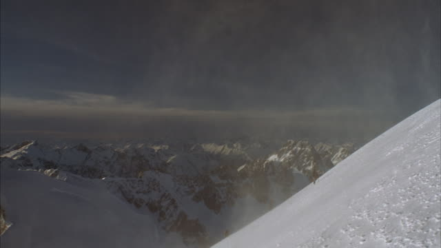 Four hikers in Tibet climb a steep snow-covered slope amidst clouds of swirling snow.
