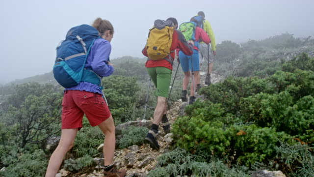 four hikers walking up a foggy mountain - climbing equipment stock videos and b-roll footage