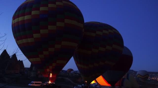 stockvideo's en b-roll-footage met vier hete lucht ballonnen bereiden om af te nemen in cappadocië tegen de blauwe hemel in de vroege ochtend. - vier dingen