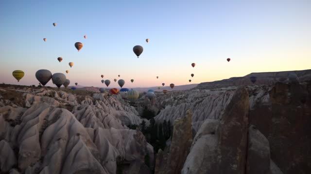 vídeos de stock e filmes b-roll de four hot air balloons at sunrise before takeoff - cappadocia, turkey - amarelo