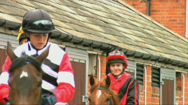 sm ms cu four jockeys riding on horses outside stable / newbury, england, uk - newbury england stock videos & royalty-free footage