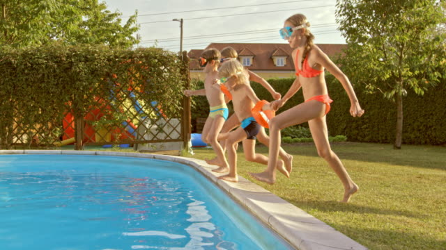 slo mo ts four kids jumping into the pool together - side view stock videos & royalty-free footage