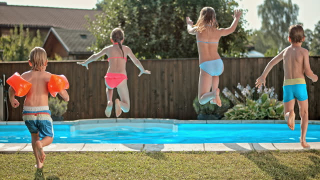 slo mo ds four kids jumping into the pool - fence stock videos & royalty-free footage