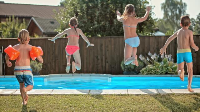 vidéos et rushes de ds au ralenti de quatre enfants de sauter dans la piscine - clôture jardin