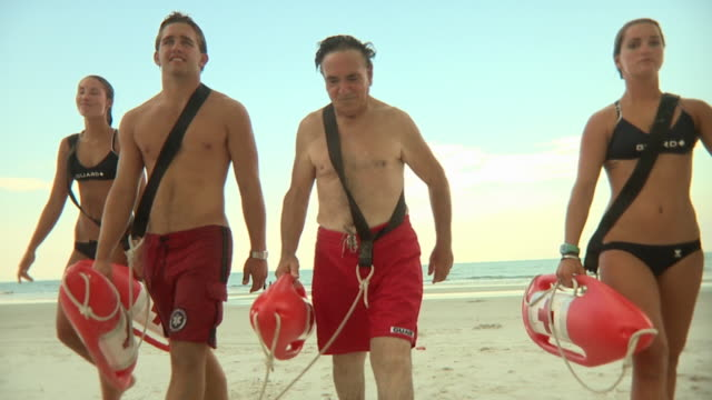 ms slo mo pov four lifeguards walking and running on beach / jacksonville, florida, usa - bagnino video stock e b–roll