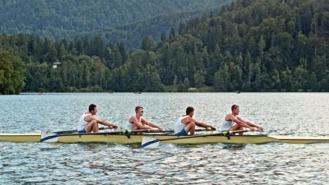slo mo ts vier männlichen athleten, die auf einem see rudern - rudern stock-videos und b-roll-filmmaterial