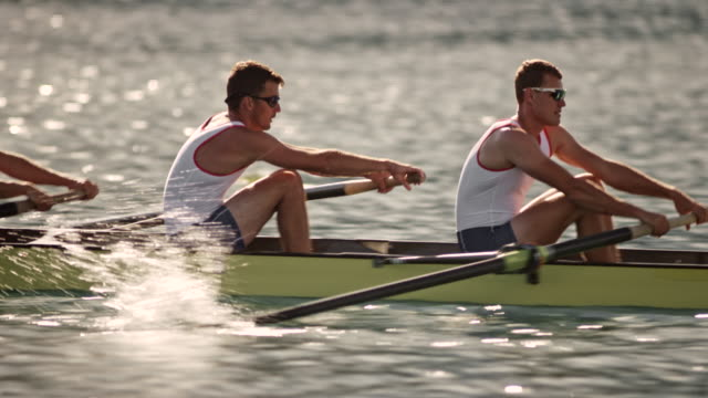 ts four male athletes rowing on a lake - competizione video stock e b–roll