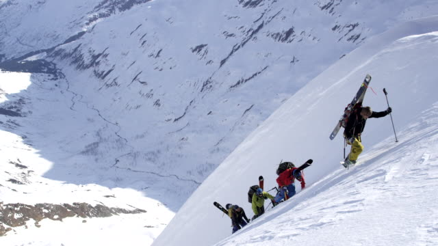 Four men bootpacking up steep mountian