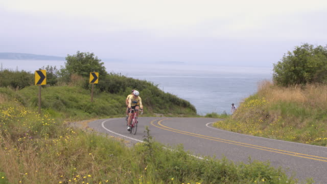 four men cycling on a rural road by a sea - ross sea stock videos & royalty-free footage