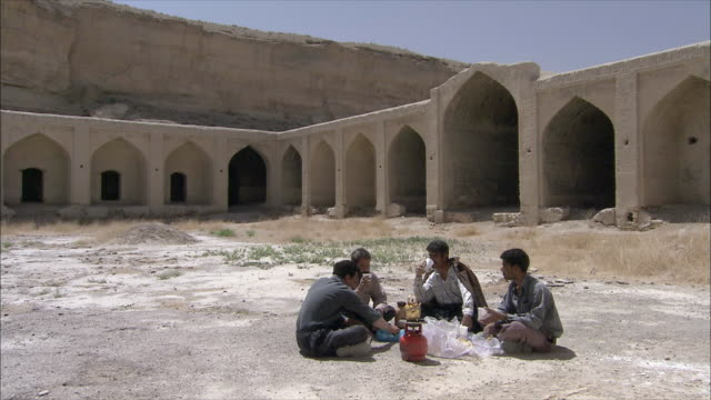 WS Four men drinking tea in courtyard of caravanserai, Iran