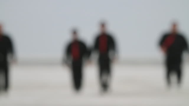 WS Four men in black clothes and red ties walking across beach / Jacksonville, Florida, USA